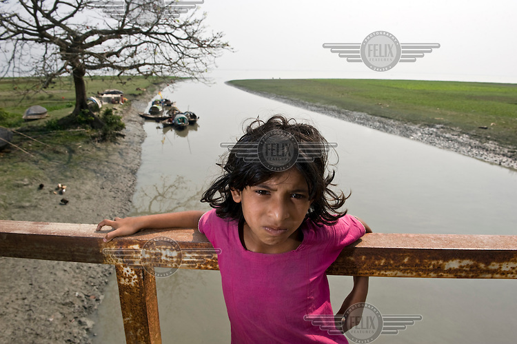 A girl stands on a bridge over a river in the Patuakhali district.