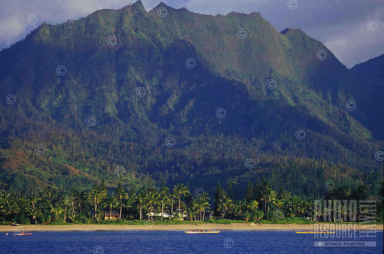 Hanalei Bay's Na Molokama mountain, with Hawaiian canoe paddlers off Hanalei Beach, North Shore, Kauai, Hawaii
