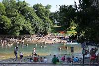 Swimmer's fill the refreshing swimming hole at Barton Springs Spillway on a hot summer's day in Austin, Texas.