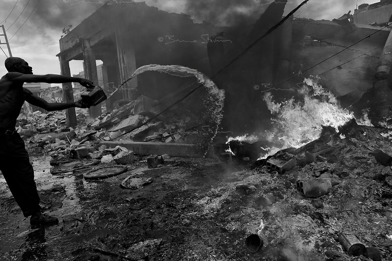 Port Au Prince, Haiti, Jan 25 2010.Monsieur train tries to put out a fire in front of what used to be his home..