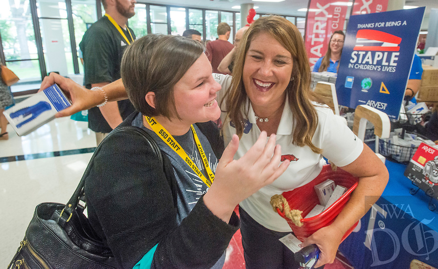 NWA Democrat-Gazette/BEN GOFF @NWABENGOFF<br /> Whitney Perkins (left), a teacher at Southwest Junior High, hugs Julie Shook with Arvest Bank, who's daughter attends Southwest, Thursday, Aug. 9, 2018, during the 52nd Annual Sam's Furniture Springdale Teacher Appreciation Day at Springdale High School. Arvest Bank was handing out free staplers to teachers at the event. More than 85 vendors set up to provide information and more than $40,000 in gifts and prizes to some 2,000 teachers and staff of Springdale Public Schools.