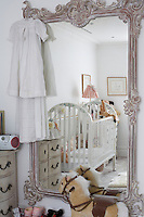In this child's room an ornately carved full-length mirrror and painted chest-of-drawers create the feeling of 18th century France