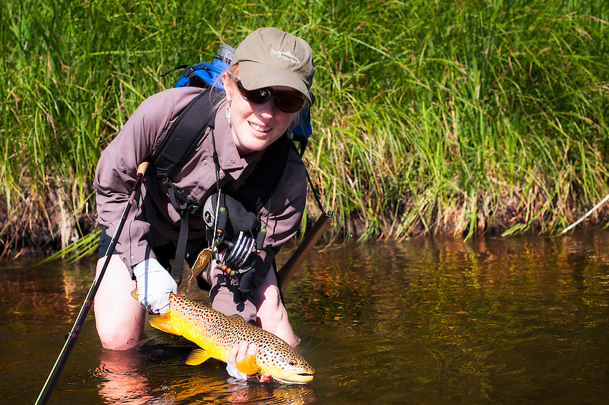 A woman holds a brown trout on the Smith River near White Sulphur Springs, Montana.