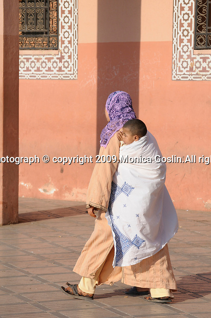 A woman with a child on her back walks through the streets in Marrakesh, Morocco.