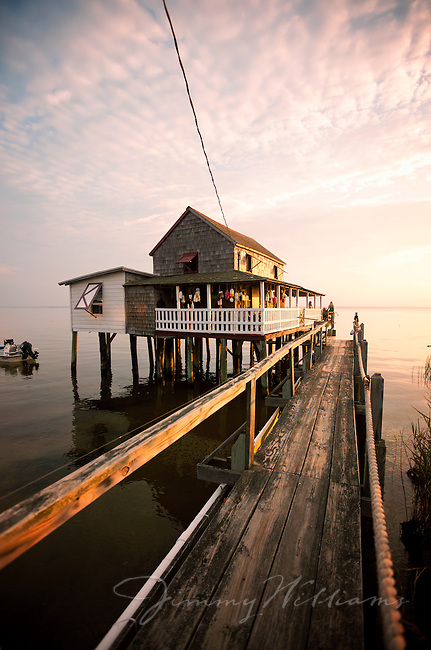 A wooden walkway takes you to the front porch of a waterfront beach cottage