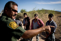 A border patrol agent lines up a group of immigrants caught while passing through the desert along Highway 286 and 86 in Tucson, Arizona, Friday, June 10, 2009. When migrants are found by the Border Patrol they are returned to the border where many will attempt  the five day travel to get into the United States several times...PHOTOS/ MATT NAGER