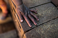 A sunburned hand of a young girl worker is seen on a pile of bricks at a brick factory in the outskirts of Puno, Peru, 2 August 2012. Child labour is a common practice at the artisanal brick factories, found predominantly in socially deprived areas of the urban zones. Poverty and lack of employment force parents, mainly season workers coming from rural areas of the country, to employ their own children, in an effort to ensure the livelihood for the whole family. Children aged 4-7 take part in simple jobs while children aged 8 and up tend to work regularly, same as adults. A family group, consisting of 2 adults and 2-3 children, may earn 20-25 USD per day, working almost the whole day, often in harsh climatic conditions.