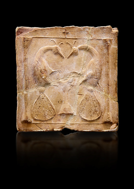 6th-7th Century Eastern Roman Byzantine  Christian Terracotta tiles depicting two Peacocks - Produced in Byzacena -  present day Tunisia. <br /> <br /> <br /> The patterns of peacock tails contain round decorations. These were seen to be the symbolic eyes of omnipotence and often ascribed to the Archangel Michael. The peacock's feather is sometimes associated with St. Barbara Also, The peacock, (due to an ancient myth that Peacock flesh did not decay), is seen as a symbol of immortality.<br /> <br /> These early Christian terracotta tiles were mass produced thanks to moulds. Their quadrangular, square or rectangular shape as well as the standardised sizes in use in the different regions were determined by their architectonic function and were designed to facilitate their assembly according to various combinations to decorate large flat surfaces of walls or ceilings. <br /> <br /> Byzacena stood out for its use of biblical and hagiographic themes and a richer variety of animals, birds and roses. Some deer and lions were obviously inspired from Zeugitana prototypes attesting to the pre-existence of this province's production with respect to that of Byzacena. The rules governing this art are similar to those that applied to late Roman and Christian art with, in the case of Byzacena, an obvious popular connotation. Its distinguishing features are flatness, a predilection for symmetrical compositions, frontal and lateral representations, the absence of tridimensional attitudes and the naivety of some details (large eyes, pointed chins). Mass production enabled this type of decoration to be widely used at little cost and it played a role as ideograms and for teaching catechism through pictures. Painting, now often faded, enhanced motifs in relief or enriched them with additional details to break their repetitive monotony.<br /> <br /> The Bardo National Museum Tunis, Tunisia.  Against a black background.