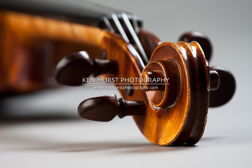 View of the scroll of a classical violin or fiddle on a grey background.