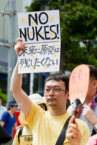 July 16, 2012 - Tokyo, Japan - A protestor holds up a anti-nuclear sign board on the streets in downtown Tokyo during the massive 100,000 people's call demanding the abolishment of all nuclear power plants. Since the recently resumed operations of the Oi Nuclear Power Plant in Fukui Prefecture, has attracted an ever growing number of anti-nuclear demonstrators in a call to stop all forms of nuclear energy. (Photo by Christopher Jue/AFLO)