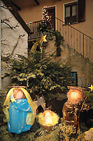 "Switzerland. Canton Tessin. Vira Gambarogno. The old town shows an exhibit of various Nativity scenes, illuminated at night for the Christmas holiday season. A Nativity Scene, may be used to describe any depiction of the Nativity of Jesus in art, but in the sense covered here, also called a crib or in North America and France a crèche (meaning ""crib"" or ""manger"" in French). It means a three-dimensional folk art depiction of the birth or birthplace of Jesus, either sculpted or using two-dimensional (cut-out) figures arranged in a three-dimensional setting. Christian nativity scenes, in two dimensions (drawings, paintings, icons, etc.) or three (sculpture or other three-dimensional crafts), usually show Jesus in a manger, Joseph and Mary in a barn (or cave) intended to accommodate farm animals. The Star of Bethlehem. Fir. © 2007 Didier Ruef"