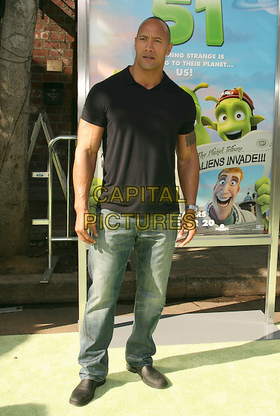 "DWAYNE ""THE ROCK"" JOHNSON .The Premiere of Columbia Pictures ""PLANET 51"" held at The Mann Village Theatre, Westwood, California, USA, .14th November 2009..full length jeans black t-shirt polo collar tattoo  .CAP/ADM/MJ.©Michael Jade/AdMedia/Capital Pictures."