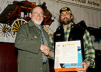 Rick Casillo  receives Most Improved Musher Award from Congressmen Don Young.  Casillo will have the use of a satellite phone for a year.