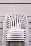 Stacked  grey lawn chairs along side of house