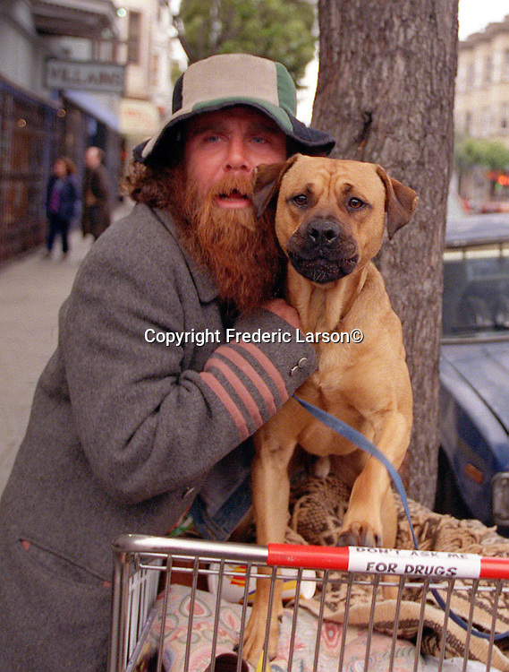 Garland holds his dog back from attacking another male dog that came close to his shopping cart on Haight Street in San Francisco, California.