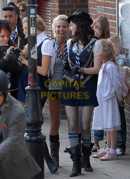 "SARAH HARDING & TALULAH RILEY.Filming on the set of ""St Trinian's: The Legend of Fritton's Gold"", outside the Globe Theatre, London, England..August 10th, 2009.2 full length black mini micro shorts grey gray top white shirt scarf striped stripes biker boots girls aloud waistcoat beige laughing profile looking over shoulder socks hat gloves film movie .CAP/IA.©Ian Allis/Capital Pictures."