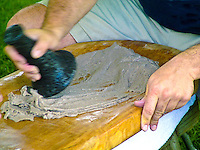 Using a poi pounder to mash cooked taro tubers or roots into a paste. Taro is sacred to Hawaiians.