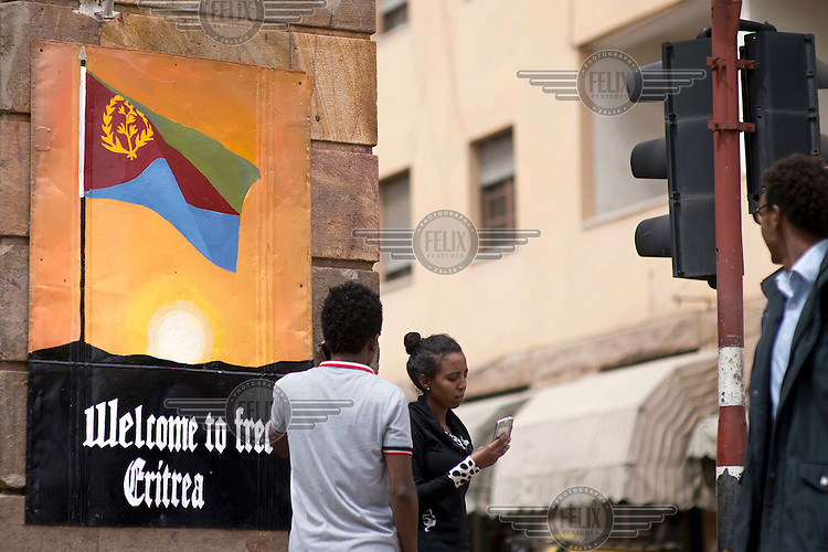 A pedestrians uses her smartphone while walking along the main road past a poster with the slogan 'Welcome to Free Eritrea', celebrating the 1991 independence.