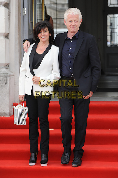 Emma Freud and Richard Curtis<br /> attends the World Premiere of 'About Time', Somerset House, London, UK, 8th August 2013.<br /> full length suit trousers popcorn bag novelty black white tuxedo jacket couple arm around navy <br /> CAP/BEL<br /> &copy;Tom Belcher/Capital Pictures