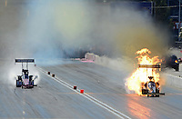Oct. 28, 2012; Las Vegas, NV, USA: NHRA top fuel dragster driver Khalid Albalooshi (right) explodes an engine as he defeats Antron Brown in the first round during the Big O Tires Nationals at The Strip in Las Vegas. Mandatory Credit: Mark J. Rebilas-