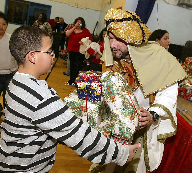 WATERBURY, CT, 01/06/08- 010609BZ01- Frank Batista Jr., 10, of Waterbury, accepts gifts for his family from &quot;King&quot; Javier Alvarado during a Three Kings Day celebration sponsored by the Hispanic Coalition of Waterbury at the River-Baldwin Recreation Center Tuesday night.  Batista said he has 4 sisters and 3 brothers.<br />  Jamison C. Bazinet Republican-American
