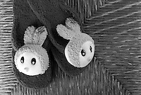 Black &amp; white stock image of pair of cute bunny slippers lying on cane background.<br />