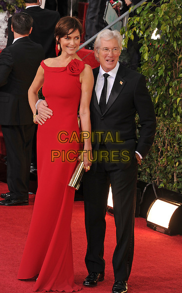 Carey Lowell & Richard Gere.Arrivals at the 70th Annual Golden Globe Awards held at the Beverly Hilton Hotel, Hollywood, California, USA..January 13th, 2013.globes full length red dress hand on hip arm around waist black suit married husband wife gold clutch bag.CAP/GAG.©GAG/Capital Pictures