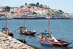 Boats used to transport wine barrels sit on the Douro River in Porto, Portugal.
