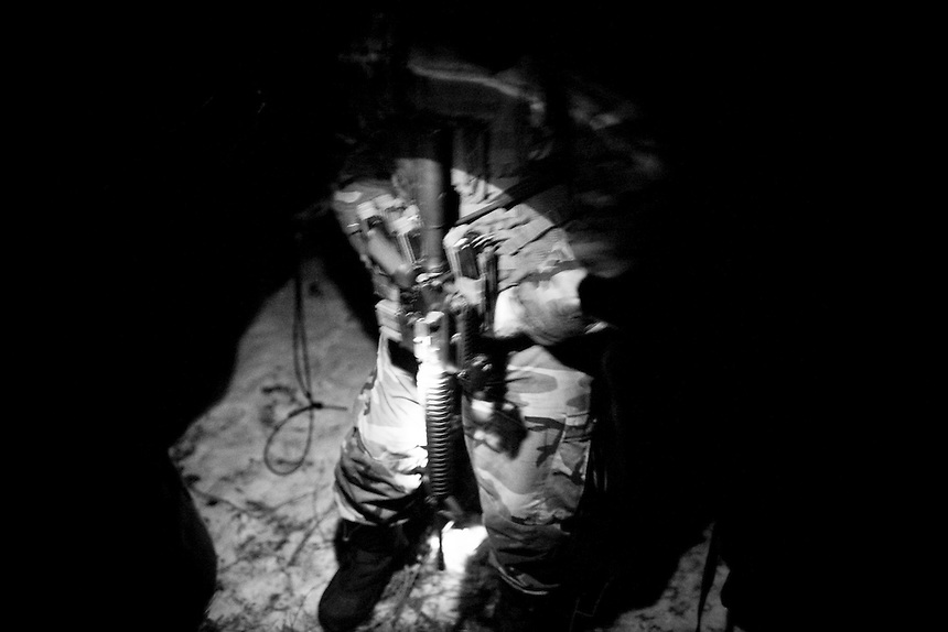 A militaman and his gun seen by flashlight in the dark of night during a training exercise in the mountains near Clark Fork, Idaho.