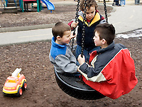 PROSPECT, CT- 13 MARCH 07- 031307JT04- .Brendan Healy and John Marchetti, both 3, listen to five-year-old Desmond Mamudi as they share a ride on the tire swing at the playground at Hotchkiss Park in Prospect on Tuesday..Josalee Thrift Republican-American