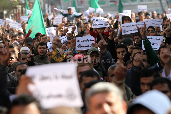 """Palestinians hold placards and shout slogans praising Islam's Prophet Mohammed during a demonstration organised by Islamist movement Hamas against the cover cartoon of the Prophet published by French satirical magazine Charlie Hebdo in Jabalia refugee camp in the northern Gaza Strip on January 23, 2015. Charlie Hebdo has printed cartoons depicting Mohammed, including one on the cover of its """"survivors"""" issue published after jihadist gunmen attacked its Paris offices, killing 12 people. Photo by Mohammed Asad"""