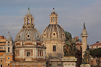 Domes of the church of Santa Maria di Loreto, 16th century, by Antonio da Sangallo the younger and the Baroque church of Santissimo Nome di Maria al Foro Traiano (Church of the Most Holy Name of Mary at the Trajan Forum), 1741 by Antoine Derizet seen from the Monumento Vittorio Emanuele II (Monument to Victor Emmanuel II) visible in the foreground, with Trajan's Column, completed in 113 AD, probably by Apollodorus of Damascus, with bronze statue of St Peter installed in 1587 by Pope Sixtus V, on their right, Trajan's Forum, Rome, Italy. Picture by Manuel Cohen