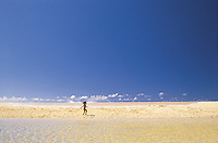 A young girl runs along a white sand beach with the beautiful blue ocean in the background.