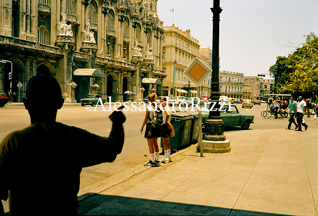 Two young girls waiting for crossing a street in Havana near Campidolio