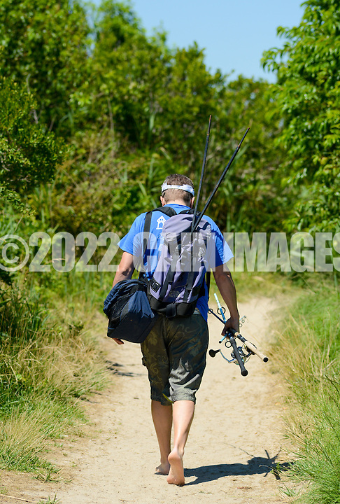 A man carries his fishing gear to the beach Saturday July 2, 2016 at Higbee Beach in Cape May, New Jersey. Photo by William Thomas Cain/Cain Images