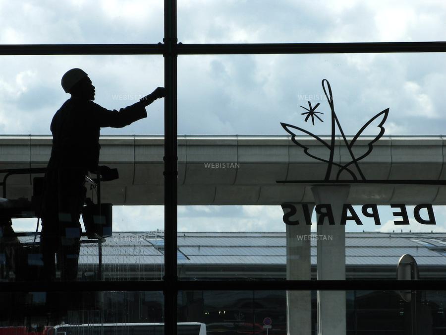 FRANCE - PARIS - 30/07/2009: Aeroport de Paris Roissy - Charles De Gaulle (CDG). Terminal 2F. Ouvrier de maintenance nettoyant les vitres. ..FRANCE - PARIS - 30/07/2009 : Paris Airport Roissy - Charles De Gaulle (CDG). Terminal 2F. Maintenance worker cleaning the windows.