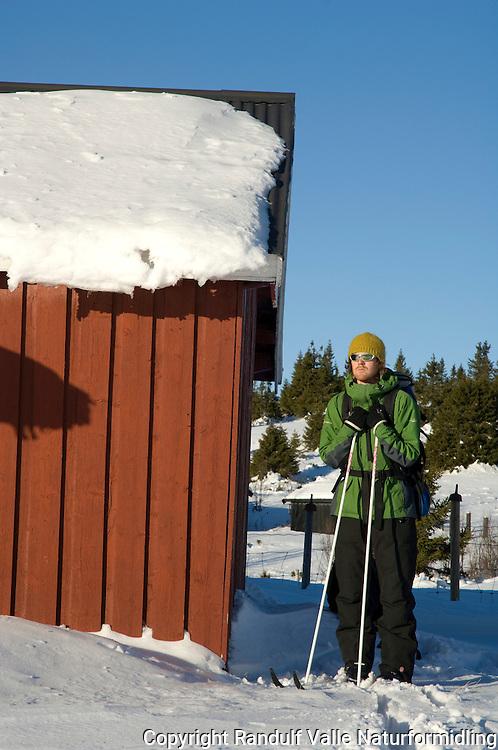 Man hviler ved en seterbygning på skitur. ---- Man resting on skiing trip.