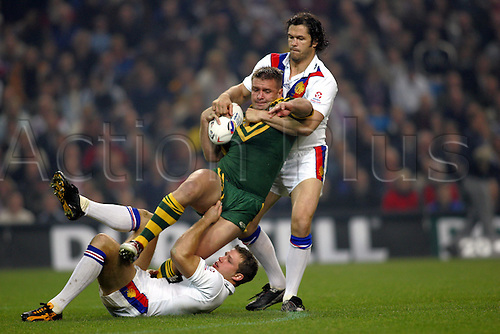 30 October 2004: Australian prop SHANE WEBCKE is tackled by Paul Wellens and Andrew Farrell during Game Three of the Gillette Tri-Nations Series between Australia and Great Britain, played at The City of Manchester Stadium, Manchester. Australia won the game 12-8 Photo: Glyn Kirk/Action Plus..041030 international rugby league player tackle tackles