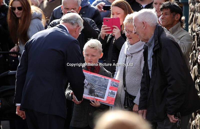 Pictured: Prince Charles speaks to a young boy with an album with pictures from the time at the Memorial Garden in Aberfan Friday 21 October 2016<br />Re: Wales has fallen silent as the country remembered the Aberfan disaster 50 years ago.<br />On 21 October 1966, a mountain of coal waste slid down into a school and houses in the Welsh village, killing 144 people, including 116 children.<br />A day of events to commemorate the disaster included a service at Aberfan Cemetery at 9:15am on Friday.<br />Prince Charles is visiting Aberfan memorial garden before unveiling a plaque in memory of the victims.<br />He will also attend a reception with the families of some of those who lost their lives, before signing a book of remembrance.
