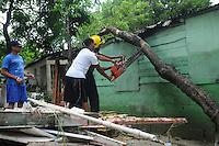 ST0108. SANTIAGO (REPÚBLICA DOMINICANA), 06/06/2011.- Dos personas cortan la rama de un árbol que cayó sobre una casa hoy, lunes 6 de junio de 2011, en Santiago (República Dominicana), donde las constantes lluvias de las últimas horas han provocado la crecida del río Licey, dejando 546 casas inundadas y 12 destruidas. EFE/José Bueno.