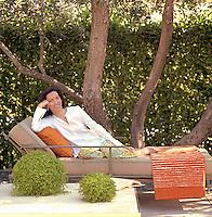 Portrait of American designer Antonia Hutt relaxing in the garden of her Los Angeles home