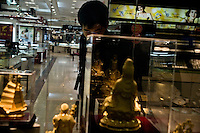 A department store worker checks on gold statues for sale in the central Xinjeikou shopping district of Nanjing, Jiangsu, China.