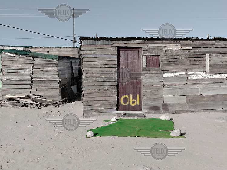 A section of green carpet has been laid before the entranc eto a wooden shack. Graeme Williams' pictures of the environments occupied by some of South Africa's poorest people focus on the interiors and exteriors of people's homes, accentuating the minutiae of the occupants' day-to-day dwelling places. The bright colours captured in these photographs are suggestive of resilience, hope and a sense of humanity that survives in these poverty-stricken communities...