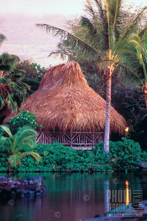 Hawaiian Hale (house) with tiki torch at Kona Village Resort on the Big Island of Hawaii