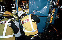Firefighters and paramedic ambulance crews attend a road traffic accident where a van carrying passengers tried to cross a level crossing and was hit by a train. The firefighters are trying to extricate the passengers from the van which has been pushed over onto its side, whilst the paramedics attend to the casualties injuries.
