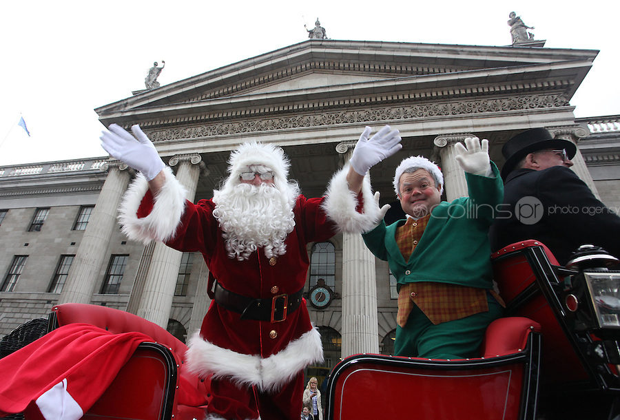 ****NO FEE PIC ******.19/11/2011.Santa Claus & Bubbles the Elf pass the GPO during a Christmas Parade.at the opening of Santa's Playland in The Ambassador Theatre,Dublin.One of this Christmas' biggest events is coming!  Santa's Playland takes up residence at The Ambassador Theatre in preparation for this year's festive season.  The spectacular event opens on Saturday 19 November and runs until Friday 23 December. Santa's Playland will see children transported to a magical Christmas paradise.On entering Santa's Playland children will be treated to a special Christmas play time.  The Play Area is full of Christmas treats with bouncy castles, slides and Christmas displays..Photo: Gareth Chaney Collins