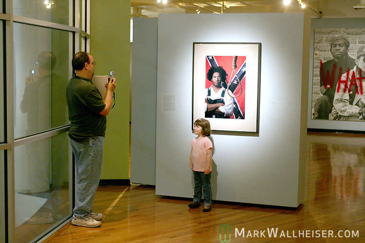 Florida State propfessor Jonathan Lieb, left, takes a photo of his three-year-old daughter Charlotte Leib in front of a photo of artist John Sims in a piece called Confederate Gothic at an art show that includes the Confederate battle flag by artist John Sims at the Mary Brogan Museum of Art and Science  March 16, 2007.    (Mark Wallheiser/TallahasseeStock.com)