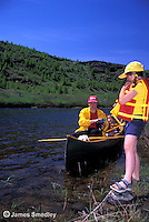 Mother letting daughter out of canoe onto shore