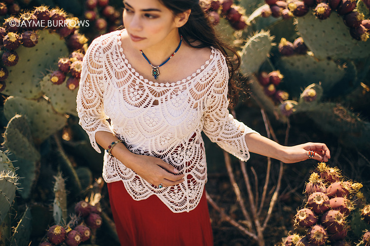 Pretty portrait of a woman surrounded by cactus with prickly pears. Focus on the hands.