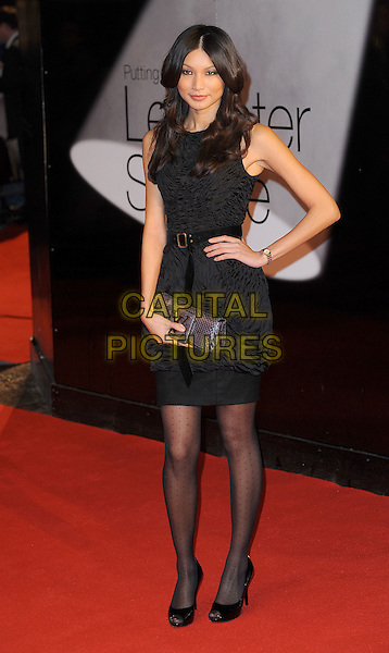 GEMMA CHAN.European Premiere of 'Brighton Rock' at the Odeon West End, Leicester Square, London, England, UK,.1st February 2011..full length sleeveless dress belt waist clutch bag tights peep toe shoes black hand on hip purple ruched polka dot patterned .CAP/BEL.©Tom Belcher/Capital Pictures.